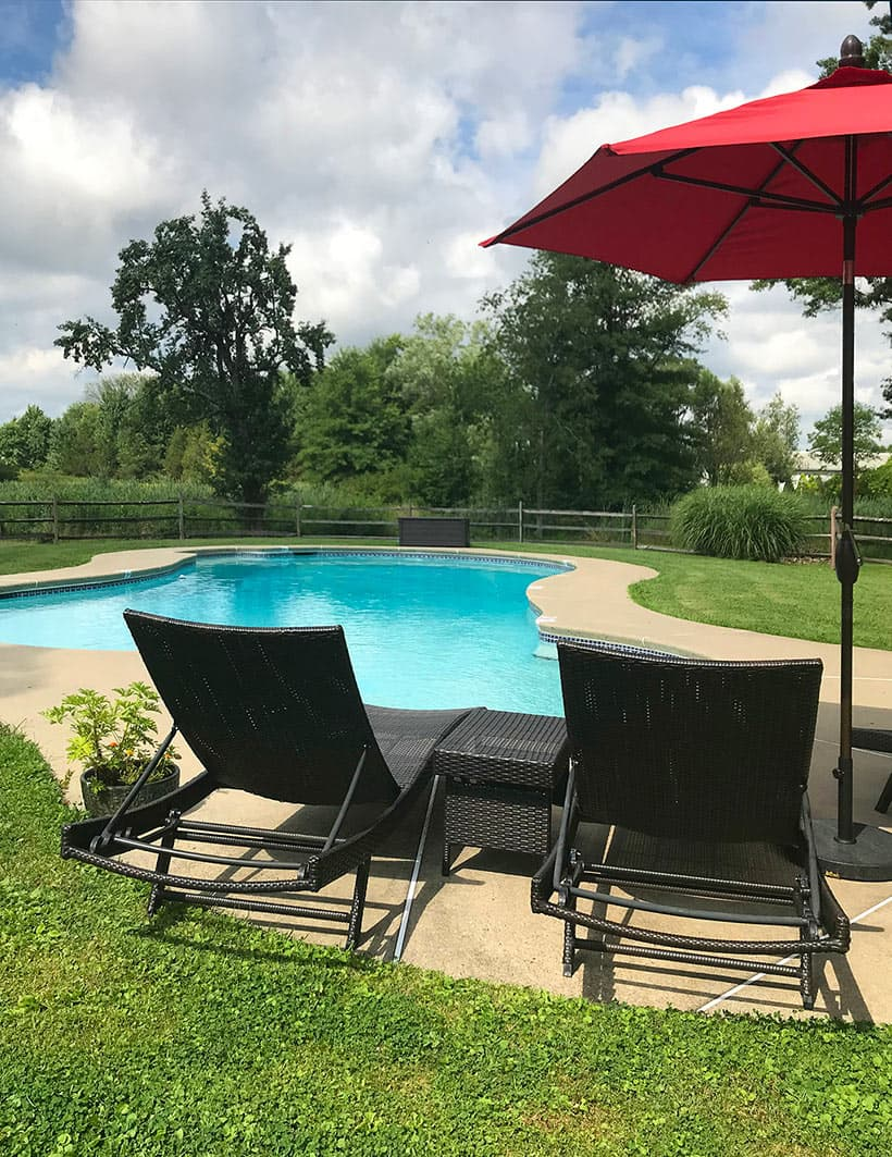 Two chairs by outdoor pool in summer