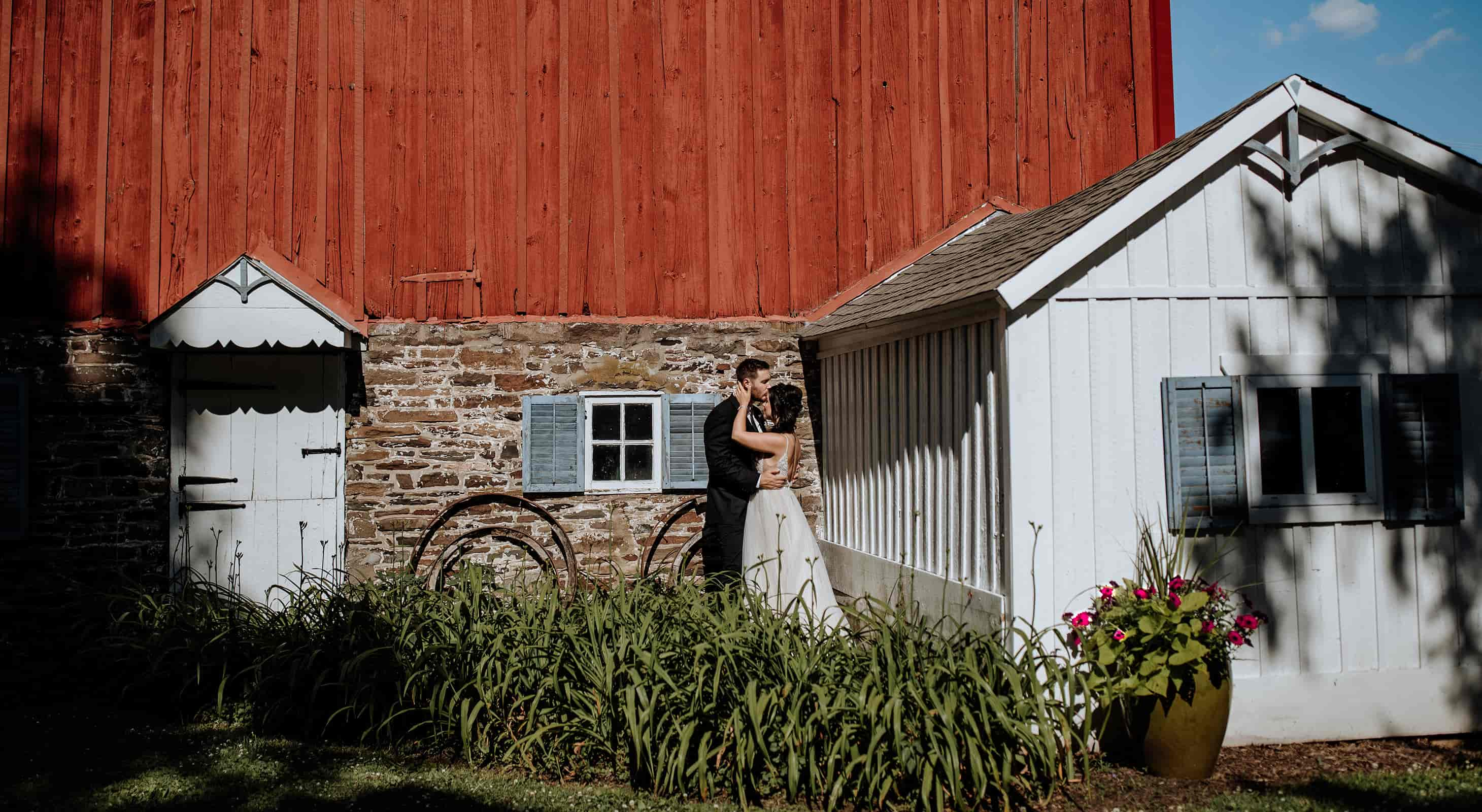 bride and groom kissing by the barn