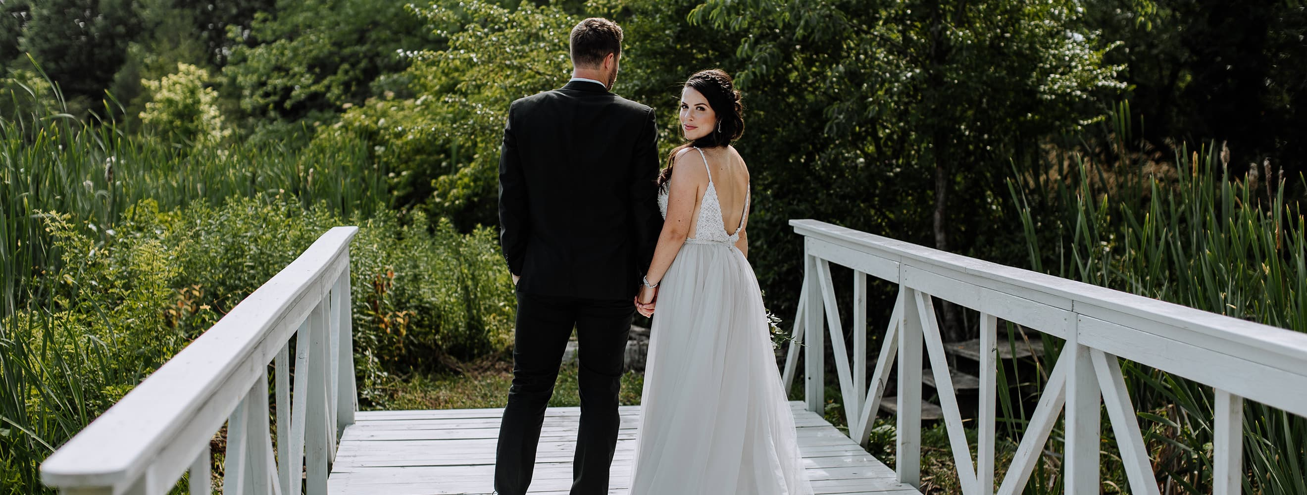newlywed couple on bridge with bride looking back over shoulder
